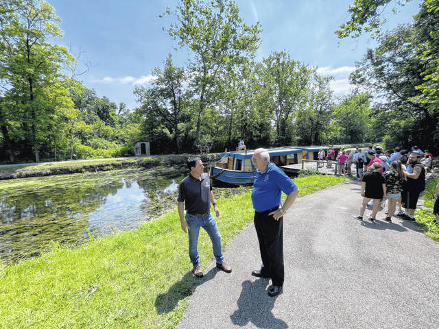 Secretary of State Frank LaRose and Sidney Mayor Mike Barhorst discuss Col. John Johnston's role in Ohio's history as they stand alongside a section of the Miami & Erie Canal as people wait to board the General Harrison, the canal boat that makes trips up and down the canal at the Johnston Farm.
