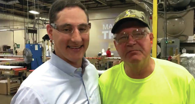 U.S. Senate candidate Josh Mandel poses with a local employee of Clopay while discussing the importance U.S. manufacturing and praising President Donald Trump.