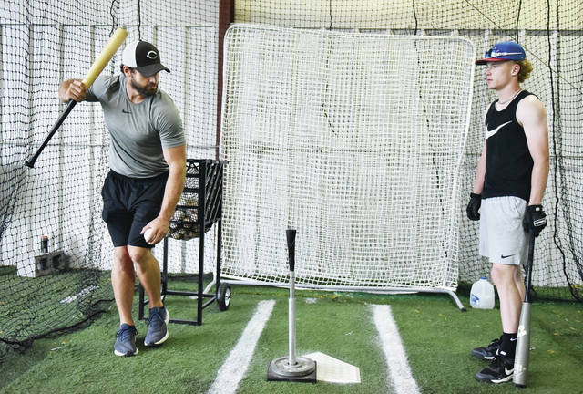 Dalton Bollinger, left, helps Ryan Schloss, right, both of Sidney, with his swing during some one-on-one training at Bollinger's indoor training facility on Wednesday, June 30. The training facility is located at 550 Folkerth Ave. in Sidney. Schloss is committed to Mount St. Joseph University for baseball.