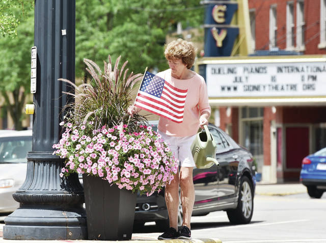Teresa Hamaker, of Sidney, places a U.S. flag into a pot of flowers at the intersection of Ohio Avenue and Poplar Street on Friday, July 2. Hamaker was helping her daughter, Sidney Alive Administrative Assistant Kristen Arnett, place the flags downtown for the 4th of July weekend. They also watered the flowers in the downtown area that were donated by Crossway Farms.