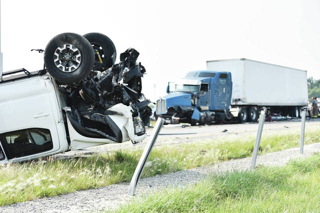 A Tacoma pickup, left, sits upside down in front of a damaged semi trailer in the south bound lane of I-75 just north of the Botkins exit on Monday, July 5. A car crashed into the back of the semi trailer and caught fire resulting in at least one fatality. A car was wedged under another semi trailer nearby. The Ohio State Highway Patrol believes there were two separate crashes involving multiple vehicles that were caused by a slow down that began due to a third crash that happened farther south on I-75. There were also numerous injuries.
