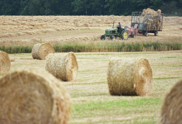 A farmer drives a tractor pulling a hay baler through a harvested wheat field located along state Route 29 just north of Sidney on Tuesday, July 6.