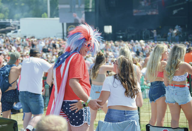 """Todd, left, and Diane Barnhart, of Delaware, Ohio, watch Neal McCoy perform at Country Concert on Thursday, July 8. Todd said """"It doesn't get any more American than this,"""" when asked why he was dressed in a wig, cape and U.S. flag shorts."""