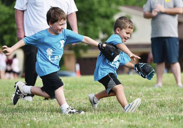 Gabe Sturm, left, 4, and Tucker Brown, 4, both of Sidney, chase down a ball while participating in Sidney-Shelby County YMCA's T-ball game on Tuesday, July 14. Gabe is the son of Adam and Natalie Sturm and Tucker is the son of Tiffany and Thomas Brown.