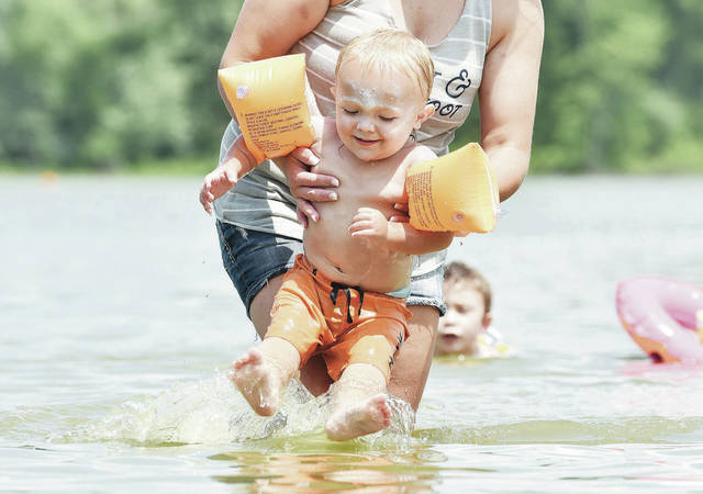 Westin Simmons, 1, is lifted up out of Lake Loramie by his mom, Christin Burnside, both of Fort Loramie, at the Lake Loramie State Park beach on Thursday, July 15. It was the first time Westin has ever swam in the lake.