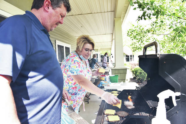 Landings of Sidney MMIT Director Michelle Stollmer, right, of Piqua, adds a slice of cheese to a burger being cooked by Facilities Manager Nick Stewart, of Sidney, at the Landings of Sidney grill-out on Tuesday, July 13. Anyone could come and pick-up a burger meal for $5.