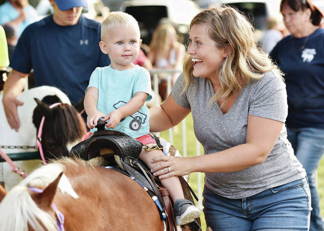 Blair Wells, left, 1, rides a pony with help from his mom, Betsy Wells, both of Anna, at the 52nd Annual Kettlersville-Van Buren Township's Fireman's Picnic on Saturday, July 17. Blair is also the son of Phillip Wells.