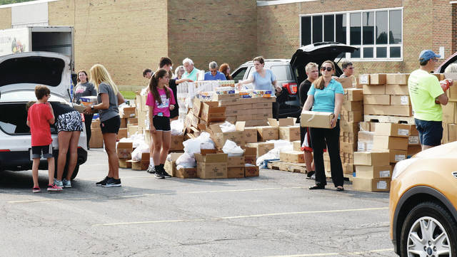 Area volunteers load food into the cars and trucks of those who wished to participate in the food giveaway held behind Sidney High School Monday, July 19 evening. A few of the food items were spaghetti and meatballs, Mac & Cheese and coffee. There was even dog and cat food for those who owned pets. Taking part in the give away were the West Ohio Food Bank, Shelby County United Way, Agape, The Sidney/Shelby County Salvation Army, the Alpha Community Center and the Holy Angels Soup Kitchen.