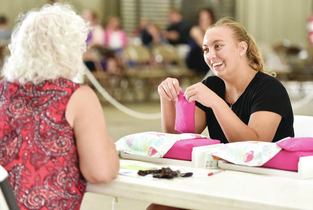 Leanne York, right, 17, of Russia, shows the doll bed she made to prefair judge Linda Beasley, of Covington, while competing in the quilting, knitting, crochet, toy, other category at the Youth Building on Wednesday, July 21. York is the daughter of Ben and Lisa York. She is a member of Russia Livestock.