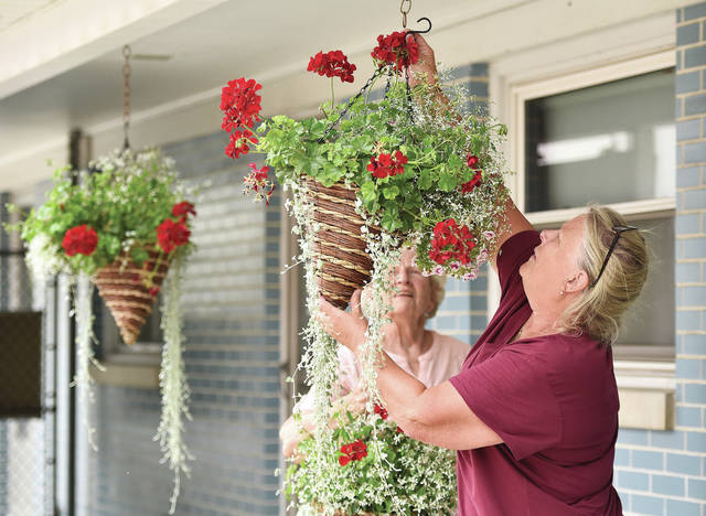Lisa Pleiman, right, of Fort Loramie, replaces one of the hanging flower baskets she is responsible for at the Dairy King and Motel in Fort Loramie on Friday, July 23. Helping Pleiman is her mom, Theresa Pleiman, of Fort Loramie.