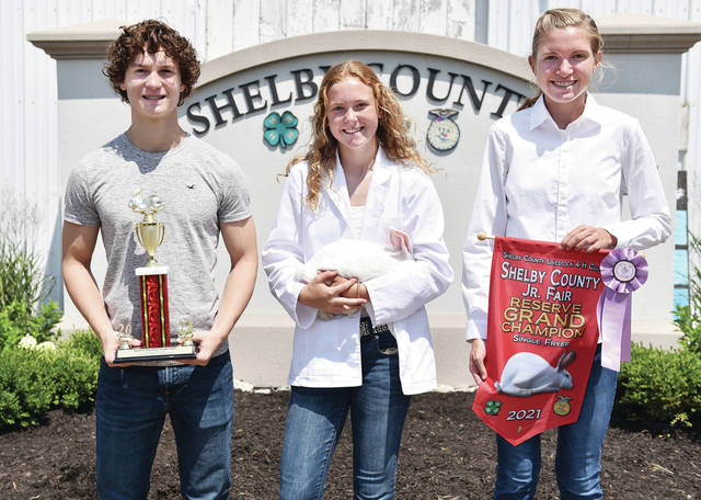 Anna Livestock member Chelsea McEldowney, center, 15, of Anna, daughter of Dale and Lisa McEldowney, won reserve grand champion single fryer rabbit at the Shelby County Fair. On the left is Xavier McEldowney, 16, and on the right is Abigail McEldowney, 16.