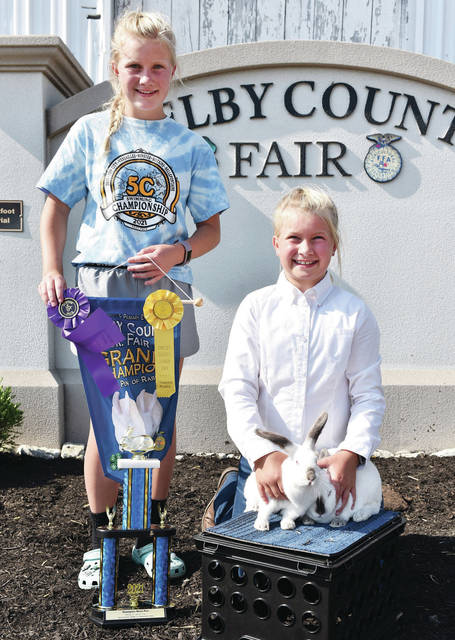 Kendall Schnippel, right, 9, of Botkins, daughter of Jana Schnippel, member of Botkins Livestock, won grand champion meat pen of rabbits at the Shelby County Fair. Quinn Schnippel, 11, left, is holding the banner.