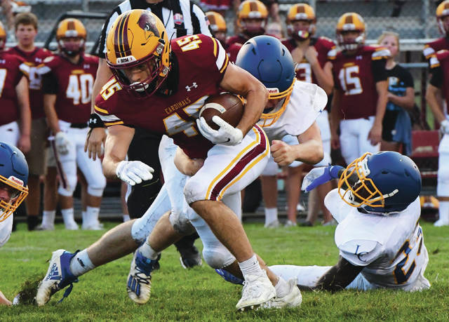 New Bremen's Colten Muether breaks through Lehman Catholic defenders during a nonconference game on Friday at Cardinal Stadium. Muether ran for 53 yards and 2 TDs on seven carries in the Cardinals' 58-0 win.