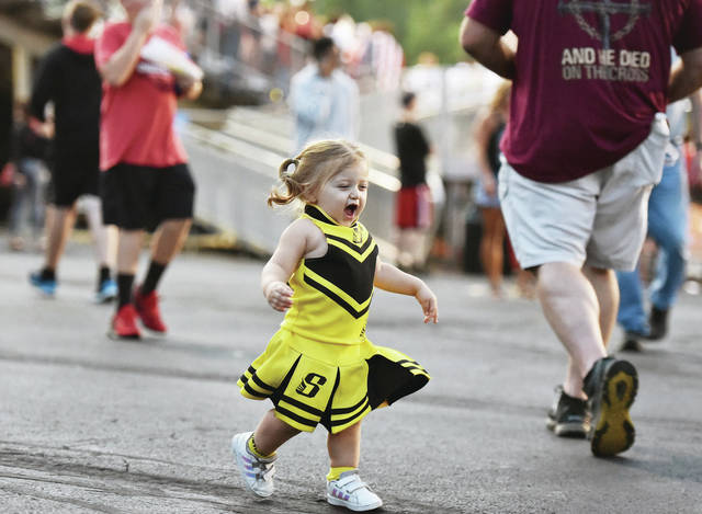 Madilyn Ferguson, 2, daughter of Baylee Ferguson, runs around the Bellfontaine football stadium at halftime of a football game between Sidney and Bellfontaine. Madilyn was wearing her custom made Sidney cheerleader outfit on Friday, Aug. 20 as she showed her support for her uncle Devon Ferguson who is a punt returner for Sidney. Madilyn also tried to get some older kids playing catch to toss her a football but she went unnoticed. The lack of attention from the older kids did not dampen Madilyn's spirits as she zipped around the stadium.