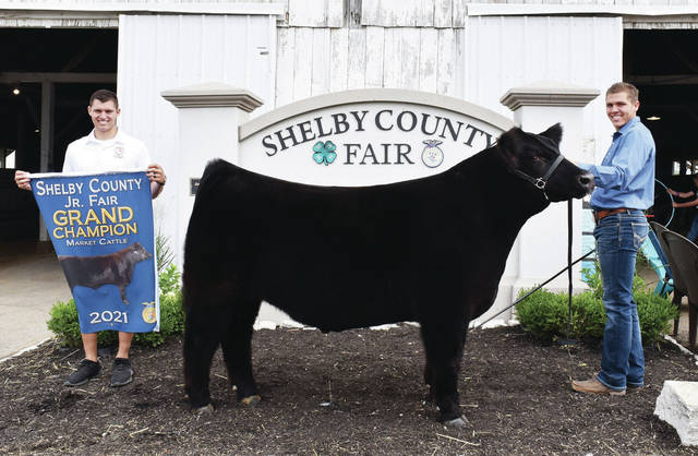 Anna Livestock 4-H Club member Hayden Huelskamp, 16, right, of Anna, son of Chad and Tonya Huelskamp, won grand champion beef steer at the Shelby County Fair. Holding the banner is Carter Huelskamp, of Anna.