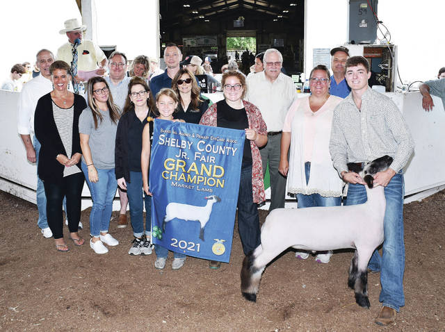 Botkins Livestock member Denton Homan, 19, of Botkins, son of Fred and Billie Homan, sells his grand champion market lamb at the Shelby County Fair on Friday, July 30, buying the lamb are Commissioner Tony Bornhorst, Botkins Family & Jackson Center Dental, Donald A. Sommer Inc., First National Bank of New Bremen, Fultz Flooring, Gaiers Chrysler Dodge Jeep, Alvetro Orthodontics, Inn Between Restaurant, Lacal Equipment, Minster Bank, Sidney Body CARSTAR, Studio 802 Salon, Sunrise Cooperative Inc., Leugers Ins/Auto Owners, Judge Jeff Beigel, and Homan Farms.