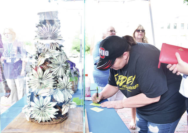 Angela Carey, of Sidney, signs up to try and win a money tree worth over $500 being offered by Wilson Health during a Relay for Life fundraiser at the 2021 Relay for Life on the courtsquare on Friday, Aug. 6.