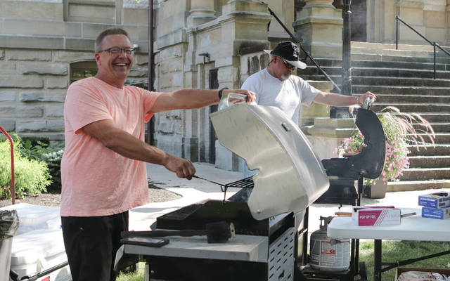 Tony Iverson and Jeremy Hatfield, members of Connection Pointe Church of God,  grilling  the brats during National Night Out activities on the Courtsquare on Tuesday, Aug. 3.