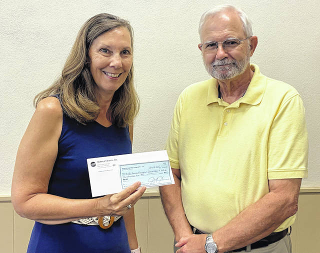 Emilie Britton, left, of the New Bremen Foundation – Blanketeers, receives a check from Chuck Gamble with the Community Connection Fund.