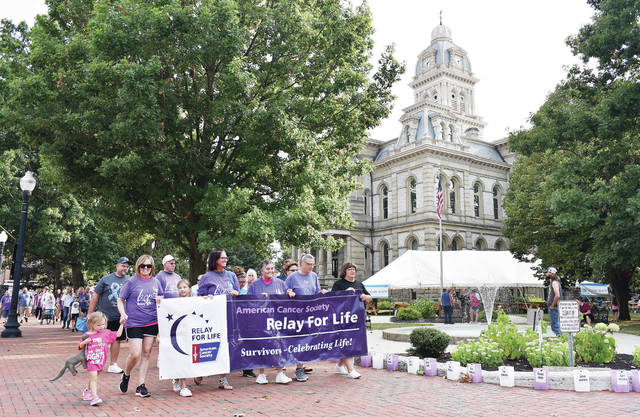 Cancer survivors take the first lap around the courtsquare at the start of the 2021 Relay For Life on Friday, Aug. 6