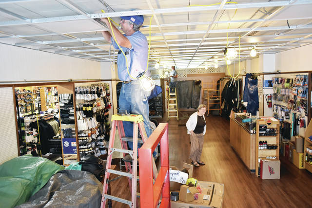 Area Electric employees Shane Bell, front, of Sidney, and Stone Weigandt, back, put up the wiring for new ceiling lights in the center room of Ron and Nita's on Thursday, Aug. 5. Walking past them is shoe store owner Nita McCrum, of Sidney. McCrum is getting the space ready to hold scrubs that she is selling at her neighboring Scrubs store that she will be closing. To make more room the the display windows were removed and new glass windows installed. The scrubs will be placed in the back half of the room.