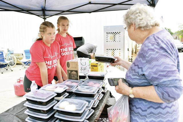 Laynee Shields, left to right, 13, of Jackson Center, and Kendall Hilbun, 12, of Botkins, sells a hotdog meal to Mary Butler, of Jackson Center, during a fundraiser next to Jackson Center Hardware on Saturday, Aug. 7. The girls were raising money to purchase AEDs for the Jackson Center community. They are also raising awareness of sudden arithmetic death syndrome that effects children. The girls were motivated after Hilbun's brother, Tanner Hilbun, 9, was diagnosed with LongQT syndrome which is a heart rhythm condition that can potentially cause fast, chaotic heartbeats.. Shields is the daughter of Misty and David Shields, and Hilbun is the daughter of Jessica and Mark Hilbun.