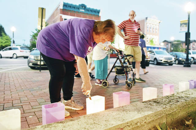 Judy Johnson, of Sidney, lights illuminaria at the 2021 Relay for Life on the courtsquare on Friday, Aug. 6. Johnson lost her husband, Benjamin Johnson, and her father, William Higgins, to cancer.