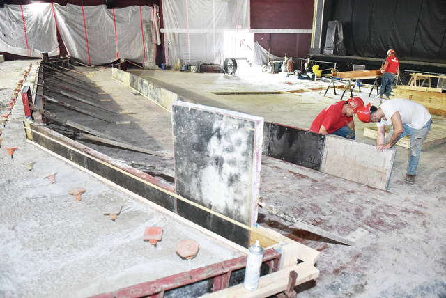 """Mike Lindeman, right, of Delphos, and Tyler Edwards, of Sidney, put up """"forms"""" that will hold wet concrete in place until it dries making the third seating level in the Historic Sidney Theatre. The wet concrete of the second level can be seen drying on the left. A total of five levels are being installed, from top to bottom, that will use enough concrete to fill up 20 concrete trucks. The flat levels will allow for tables and different forms of seating that would be difficult on the current floor which has a strong diagonal slope. Ferguson Construction expects to be finished by the end of the month."""