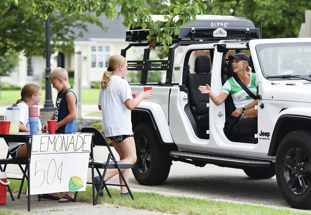 Kendall Tyler, third from left, 11, walks a glass of lemonade over to Jill and Mark Oldiges while working a lemonade stand on the north end of Minster. Working with Kendall are her sister, Lauren Tyler, far left, 13, and their neighbor, Blake Nolan, 8, all of Minster. The kids decided to set-up the stand just for fun on Thursday, Aug. 19. Lauren and Kendall are the children of Leslie and Ryan Tyler. Blake is the son of Denise and Tim Nolan.