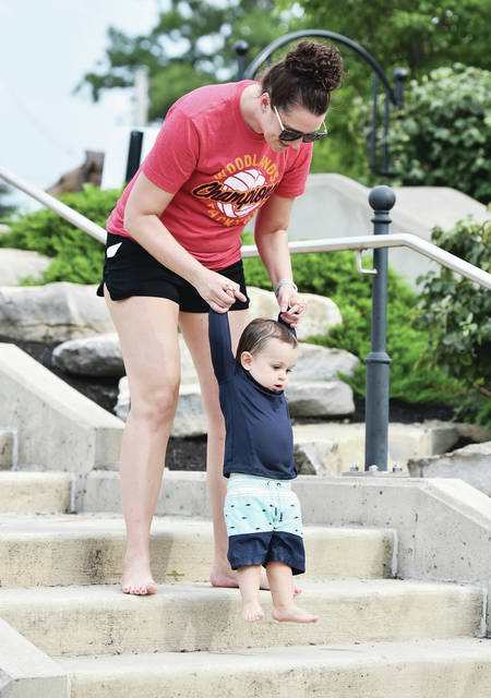 Katie Schnelle, helps her nephew, Jordan Watson, 1, both of Columbus, down the steps at Komminsk Legacy Park in New Bremen on Thursday, Aug. 19. Jordan was in town visiting his grandparents, Craig and Sue Schnelle. Jordan is the son of Liv and Corry Watson.