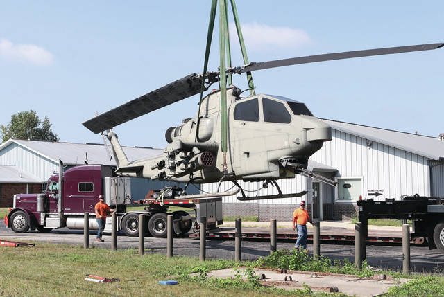 The U.S. military helicopter that has long sat in front of the old AMVETS Post 1986 building at 1319 Fourth Ave., is lifted into the air by a crane that put it down on a flatbed trailer before it was driven out of town Monday. The helicopter was removed because AMVETS Post 1986 had to leave the building due to a lack of new members causing financial issues and sold the building. The helicopter has been reissued to the city of Lebanon, Mo,m where it will be displayed at the Fallen Warriors Memorial on the northeast portion of Elm Street and Washington Street intersection within the city limits.The city has been waiting for a helicopter to join the memorial for over 10 years. Twisted Discounts, which sells liquidated items from large retailers, is now located in the former AMVETS building.