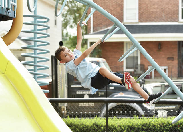 First-grader Leland O'Leary, 6, of Sidney, climbs upside-down on the Holy Angels Catholic School jungle gym on Tuesday, Aug. 24, the first day of school. The thermometer read 85 degrees while the kids were playing but everyone of them seemed impervious to the heat as they never stopped moving until recess was over. Leland is the son of Ryan and Jannel O'Leary.