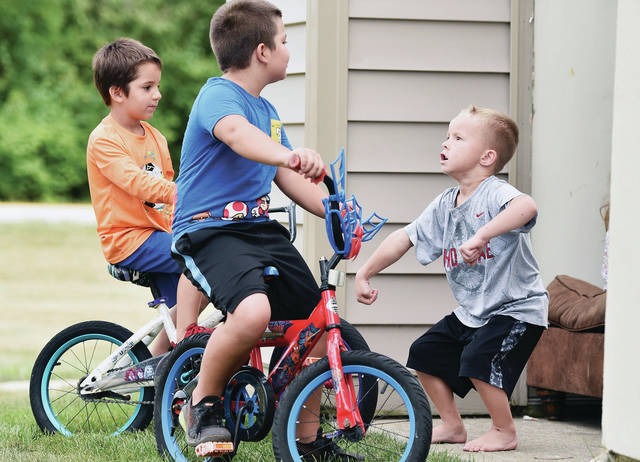 Mason Phelps, far right, 4, gets animated as he discusses bikes with his friends Colton VanHook, far left, 5, and Wyatt VanHook, 7, all of Sidney, on the eastern edge of Sidney. Mason had been drawing on the sidewalk with chalk when the brothers rode up on their bikes which drew the attention of Mason on Wednesday, Aug. 25. Mason is the son of Brittany and Aaron Phelps. Wyatt and Colton are the children of Brittany and Brandon VanHook.