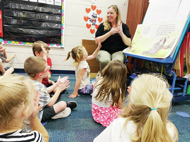 Mindy Cox reads her kindergarten class the book The Kissing Hand by Audrey Penn during reading time. It was the first day of school at Fairlawn Local Schools on Wednesday, Aug. 25.