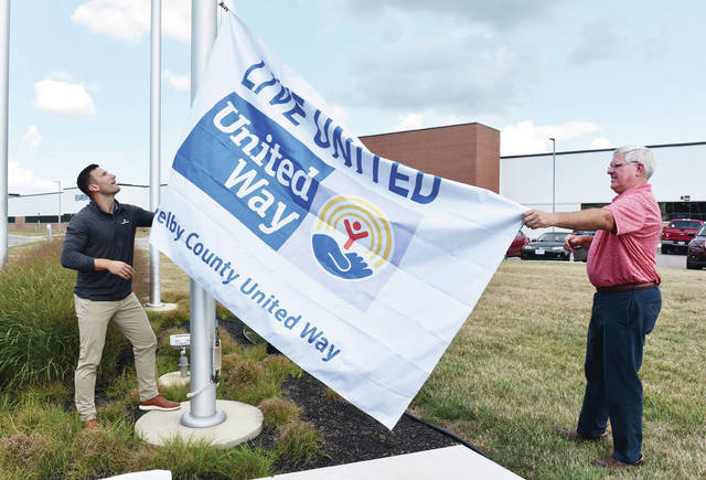 United Way Committee Chair for Emerson and Product Manager Grant Kovac, left, of Dayton, and United Way Large Manufacturing Co-Chair and Sidney Parks and Recreation Director Duane Gaier raise the Shelby County United Way flag in front of Emerson on Thursday, Aug. 26.