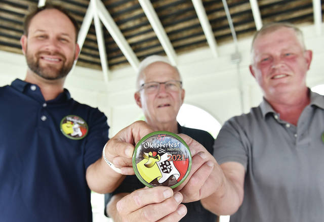 Unveiling the 2021 Minster Oktoberfest button are, left to right, Minster Oktoberfest President Adam Meyer, Minster Mayor Dennis Kitzmiller and Button House Chair Leon Mertz, all of Sidney. The button was unveiled at the Centennial Park Gazebo on Thursday, Aug. 26.