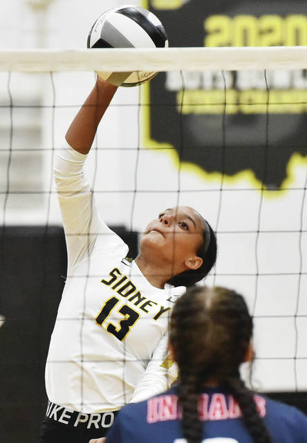 Sidney sophomore outside hitter Kyla Rush spikes against Piqua's Jordan Adkins during a Miami Valley League crossover match on Thursday in Sidney. The Yellow Jackets won 3-2 to earn their first win of the season.