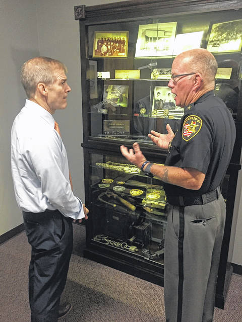 Ohio's Fourth District Republican Congressman Jim Jordan, left, visits the Shelby County Sheriff's Office Friday morning, Aug. 13. Shelby County Sheriff Jim Frye explains to Jordan the history of the sheriff's office shown in the pictures and memorabilia in the display case.