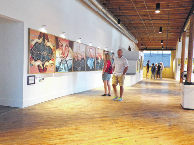 """Visitors look at Maureen O'Keefe's seven panel artwork """"We Are the Sacristans."""""""