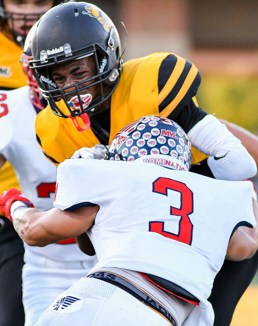 Sidney junior receiver Sam Reynolds is tackled by Piqua's Jasiah Medley after making a catch in the first half of a Miami Valley League crossover game on Friday at Sidney Memorial Stadium.