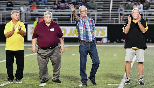 """Mike Flanagan, center, of Sidney, waves to the crowd at Sidney Memorial Stadium after being recognized during halftime of Sidney's Miami Valley League Valley Division game against Greenville on Friday. Flanagan was one of about two dozen former players, coaches and administrators in attendance on Friday for the 50th anniversary celebration of the """"30 and 0"""" teams of 1968, 1969, and 1970, when the program finished 10-0 each year. The reunion was delayed one year due to the COVID-19 pandemic. Flanagan, who played collegiately at Indiana, played all three years during the """"30 and 0"""" run and was named Sidney's most valued player for the 1970 season."""