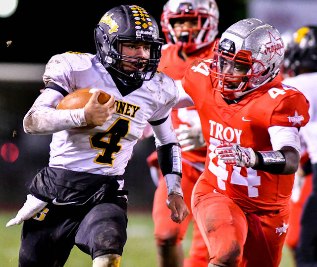 Sidney senior quarterback EJ Davis runs while trying to avoid Troy's Kristifer Williams during a Miami Valley League crossover game on Thursday at Troy Memorial Stadium. Davis played at quarterback for the first time since his freshman season in place of starter Donavin Johnson, who is battling a lingering injury.