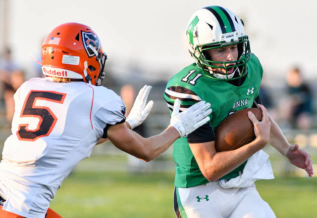 Anna junior quarterback Carter Seigle runs as Coldwater's Marcel Blasinglame closes in during a Midwest Athletic Conference game on Friday at Booster Field. Seigle threw for 129 yards with one TD and one interception for the Rockets, which lost 42-7.
