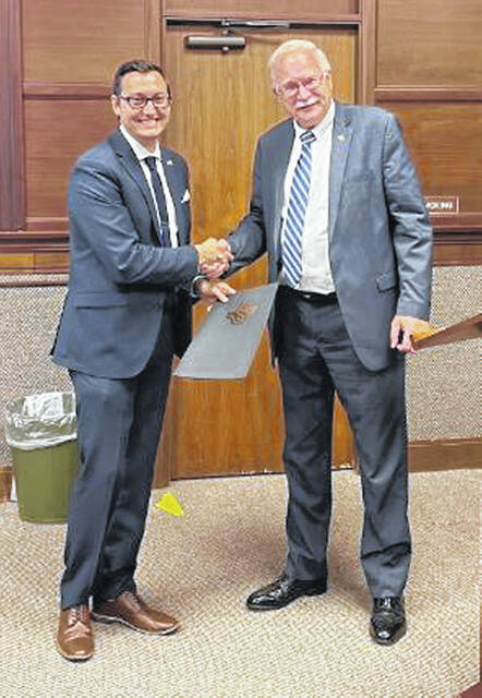 Andrew Bowsher, Sidney's next city manager, shakes hands with Mayor Mike Barhorst after Sidney City Council adopts a resolution naming him as the next city manager.