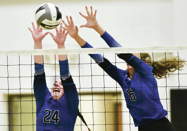 Fairlawn's Taylor Lessing, left, and Addison Swearingen try to block a spike during a Shelby County Athletic League match on Tuesday in Botkins. Lessing had 44 assists and Swearingen had 13 kills and 13 digs.