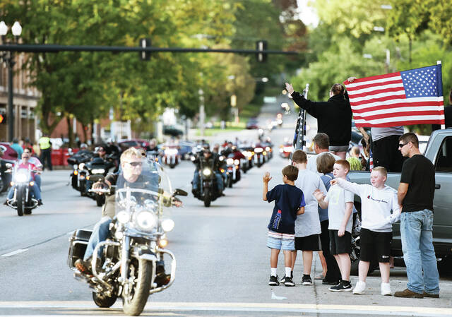 Onlookers wave and hold up a U.S. flag as a long line of motorcycles drives down Ohio Avenue and turns left onto Court Street. The motorcycles were escorting the traveling Vietnam Wall from Wapakoneta to Custenborder Field where it will be assembled and put on display starting Thursday, Sept. 16. The opening ceremony will be at 5:30 p.m.. The Vietnam Wall coming to Sidney was organized by the Shelby County Historical Society and a legion of volunteers.