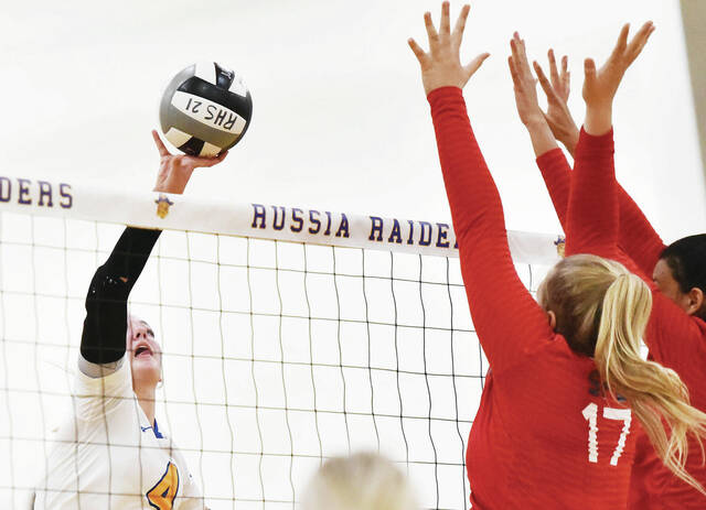 Russia's Kate Sherman spikes as Graham's Landree Bacher tries to block during a nonconference match against St. Paris Graham on Friday at Clair C. Naveau Gymnasium in Russia. Sherman led the squad with 17 kills.
