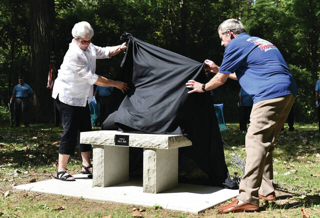 Brenda Hall, left, and Rich Wallace, both of Sidney, unveil a memorial bench for Hall's husband Jim Hall at the Tawawa Civic Park 4th Annual Cruise-In organized by the Shelby County Historical Society on Saturday, Sept. 18. Jim was known for working with veterans, he was a historical society board member and active in the Sidney 1st United Methodist Church.