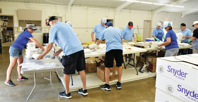 Members of the Sidney Kiwanis Club form an assembly line putting together chicken dinners on Monday, Sept. 6. The chicken dinner sales will support the Sidney Kiwanis Club Scholarship program.