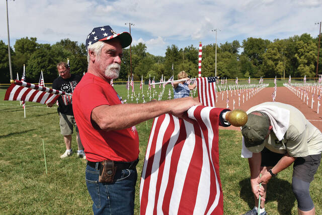 U.S. Army Veteran Will Fogt, of Anna, rolls up a U.S. flag as the Field of Crosses is taken down on Sunday, Sept. 19. at Custenborder Field.